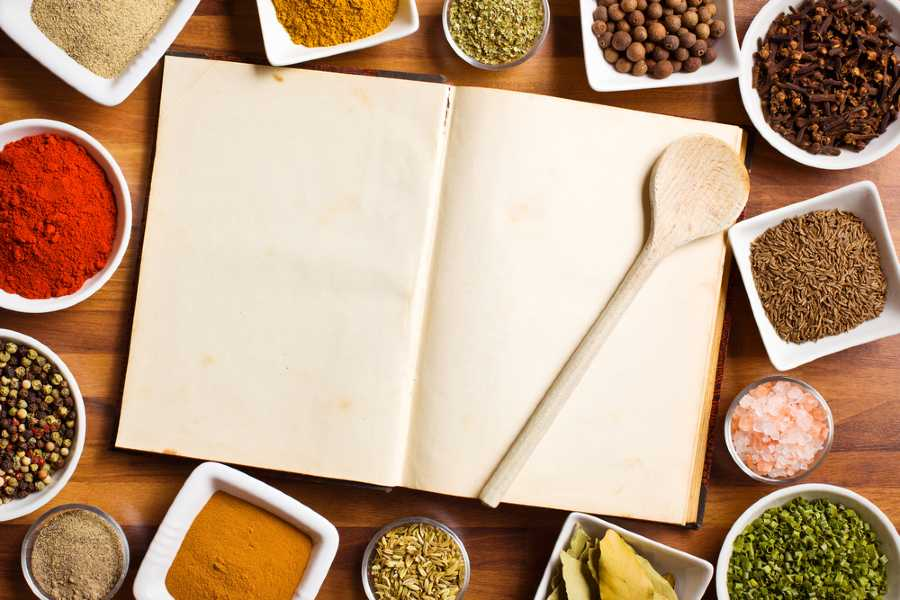 blank book surrounded by spices