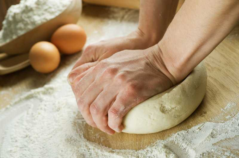 person kneading dough by hand