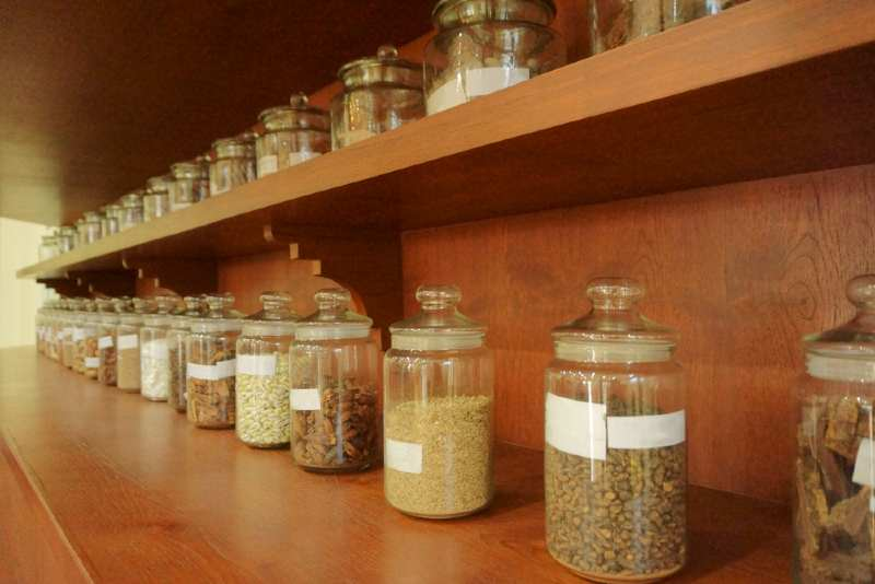 collection of jars full of herbs on a worktop