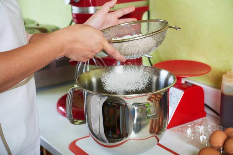 baker sieving flour