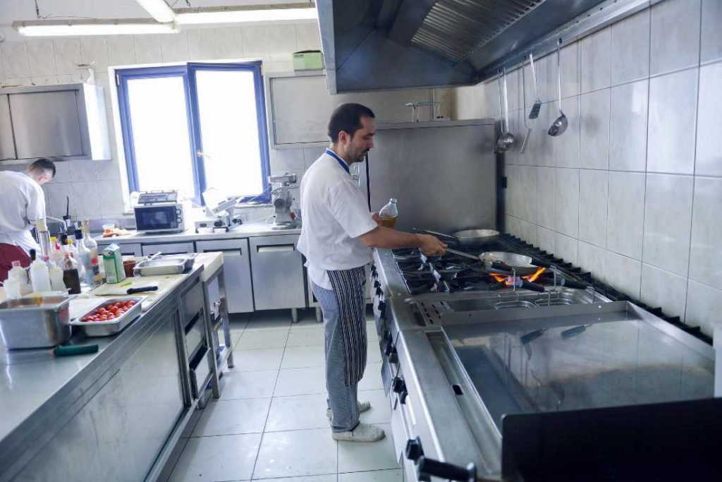 chef standing up next to a hob
