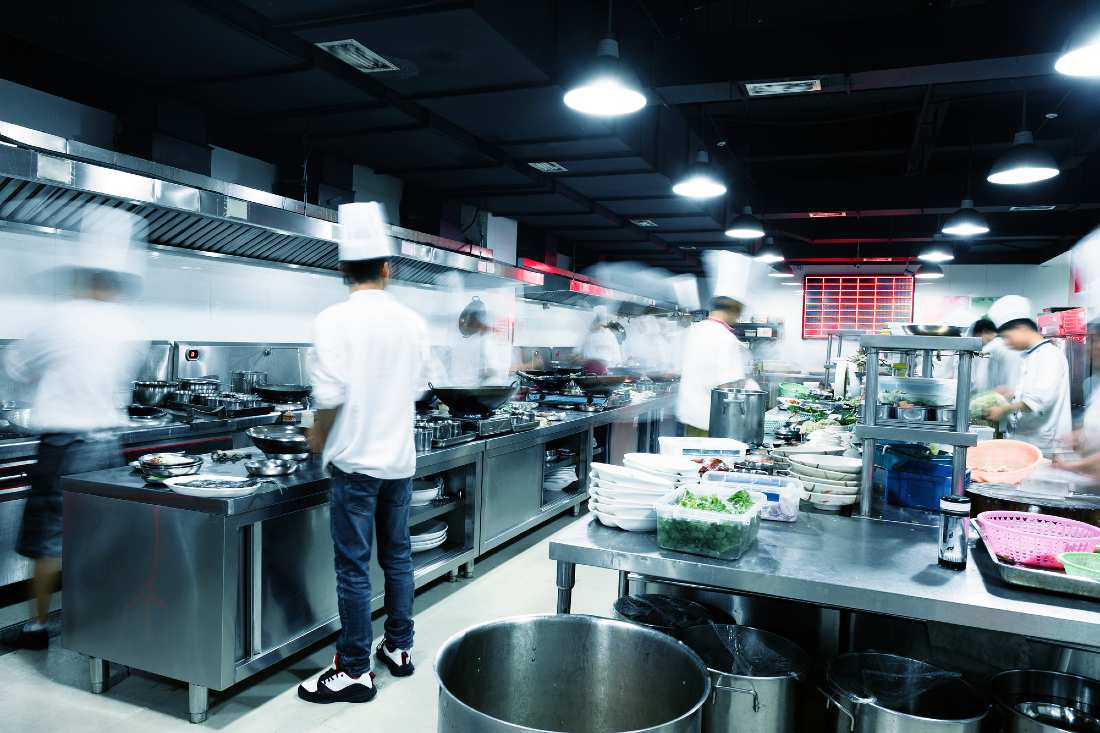 chefs standing and cooking in a busy kitchen